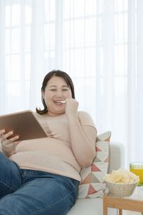タブレットPCを見る太った女性の写真素材 [FYI03146072]