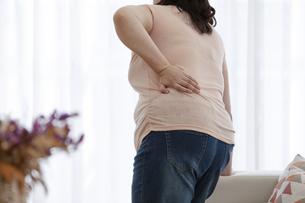 腰痛に苦しむ太った女性の写真素材 [FYI03146096]
