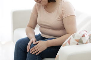 膝を押さえる太った女性の写真素材 [FYI03146097]