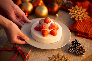 クリスマス小物とケーキを置く手元の写真素材 [FYI03146161]