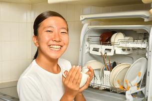 食洗器で食器を洗浄する女の子の写真素材 [FYI03146204]