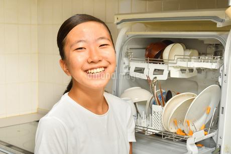 食洗器で食器を洗浄する女の子の写真素材 [FYI03146207]