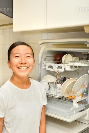 食洗器で食器を洗浄する女の子の写真素材 [FYI03146211]