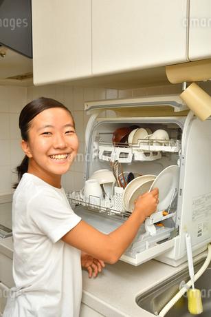 食洗器で食器を洗浄する女の子の写真素材 [FYI03146214]