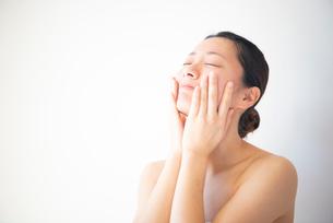 顔を触っている女性のビューティーイメージの写真素材 [FYI03147443]