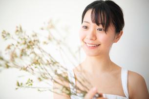 花を持って笑っている女性の写真素材 [FYI03147448]