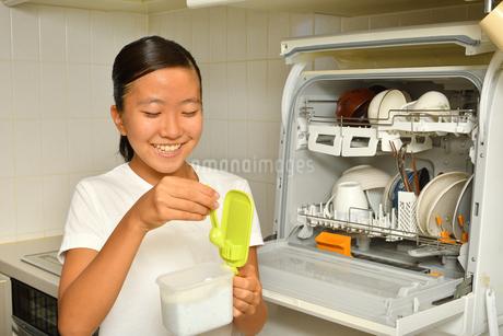食洗器で食器を洗浄する女の子の写真素材 [FYI03147907]