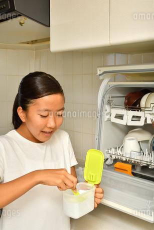 食洗器で食器を洗浄する女の子の写真素材 [FYI03147908]