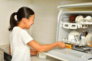 食洗器で食器を洗浄する女の子の写真素材 [FYI03147909]