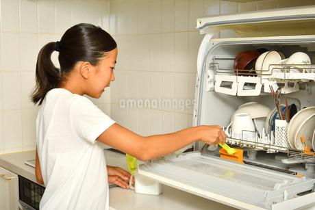 食洗器で食器を洗浄する女の子の写真素材 [FYI03147910]