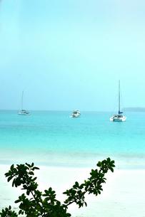 ニューカレドニア・イル・デ・パンのクトビーチの白い砂浜と透き通った青い海に浮かぶ三隻の船の写真素材 [FYI03148279]