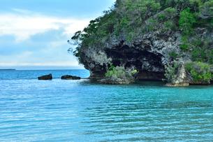 ニューカレドニア・イル・デ・パンのカヌメラ・ビーチの洞窟のある岩と青い海の写真素材 [FYI03148384]