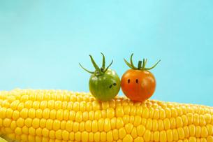 とうもろこしに乗った顔のある可愛い恋するミニトマトのカップルの写真素材 [FYI03148911]