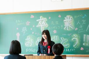 黒板の前に立ち微笑む女子学生の写真素材 [FYI03149334]