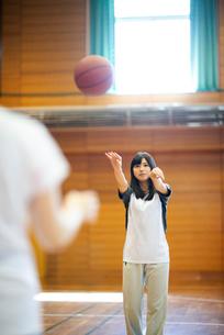 体育館でバスケットをする女子学生の写真素材 [FYI03149349]