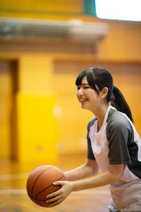 体育館でバスケットボールをする女子学生の写真素材 [FYI03149359]