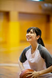 体育館でバスケットボールをする女子学生の写真素材 [FYI03149360]