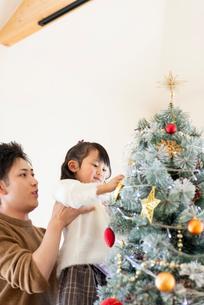 クリスマスツリーの飾り付けをする親子の写真素材 [FYI03149548]