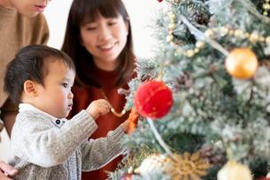 クリスマスツリーの飾り付けをする親子の写真素材 [FYI03149549]