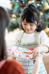 アイシングクッキーを持ち微笑む女の子の写真素材 [FYI03149607]