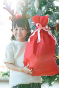 クリスマスプレゼントを持ち微笑む女の子の写真素材 [FYI03149609]