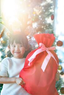 クリスマスプレゼントを持ち微笑む女の子の写真素材 [FYI03149611]