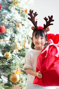 クリスマスプレゼントを持ち微笑む女の子の写真素材 [FYI03149613]