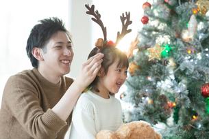 クリスマスツリーの前で微笑む親子の写真素材 [FYI03149619]