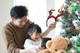クリスマスツリーの前で微笑む親子の写真素材 [FYI03149620]