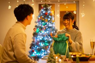クリスマスプレゼントを持ち微笑むカップルの写真素材 [FYI03149832]
