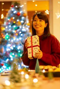 クリスマスプレゼントを持ち微笑む女性の写真素材 [FYI03149833]