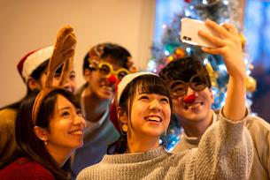 クリスマスパーティーで記念写真を撮る若者たちの写真素材 [FYI03149840]