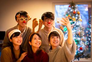 クリスマスパーティーで記念写真を撮る若者たちの写真素材 [FYI03149841]