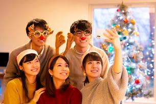 クリスマスパーティーで記念写真を撮る若者たちの写真素材 [FYI03149842]