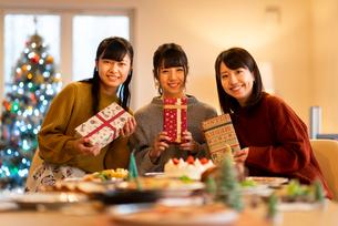 クリスマスパーティーでプレゼントを持ち微笑む女性の写真素材 [FYI03149845]