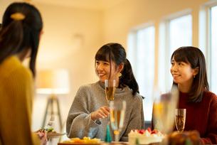 クリスマスパーティーで談笑をする若者たちの写真素材 [FYI03149849]