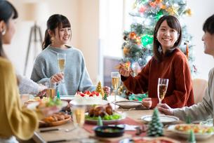 クリスマスパーティーで談笑をする若者たちの写真素材 [FYI03149908]