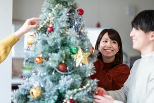 クリスマスツリーに飾り付けをする若者たちの写真素材 [FYI03149936]
