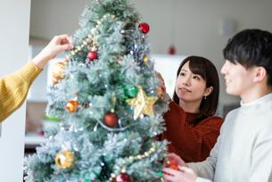 クリスマスツリーに飾り付けをする若者たちの写真素材 [FYI03149938]