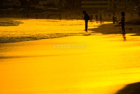 夕暮れの波打ち際で遊ぶ子供の写真素材 [FYI03150871]