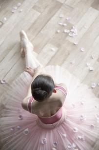 床に座るバレリーナと花びらの写真素材 [FYI03151088]