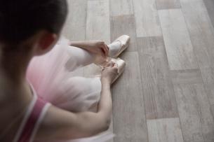 床に座ってトゥシューズを履くバレリーナの写真素材 [FYI03151091]