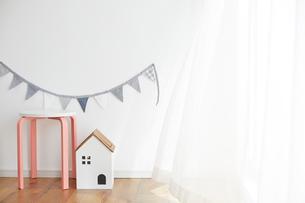 壁の前にあるガーランドと丸いすと家の形のゴミ箱の写真素材 [FYI03151308]