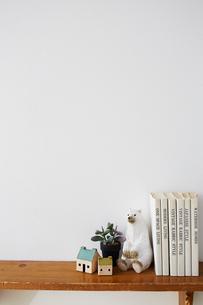 白い壁につけられた雑貨や本が乗っている茶色の棚の写真素材 [FYI03151314]