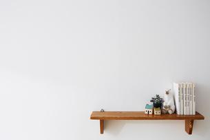 白い壁につけられた雑貨や本が乗っている茶色の棚の写真素材 [FYI03151315]
