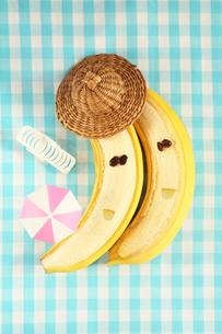 麦わら帽子を被った可愛いい顔のあるバナナのカップルとイスとパラソルの写真素材 [FYI03151885]