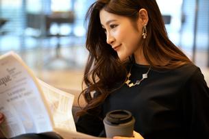 新聞を読む女性の写真素材 [FYI03152558]