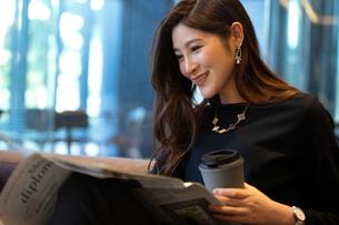 新聞を読む女性の写真素材 [FYI03152560]