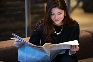 新聞を読む女性の写真素材 [FYI03152563]
