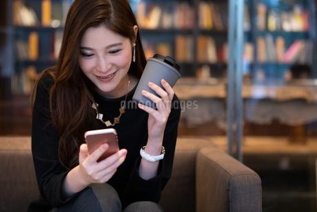 ソファーでスマホを見る女性の写真素材 [FYI03152564]